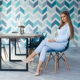 Stylish woman in modern interior. Young beautiful woman with long straight blond hair in blue suit sitting at wooden table in stylish modern interior. Natural Stock Photo