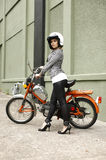 Stylish woman with moped. Portrait of a young and stylish woman with a moped Royalty Free Stock Photos