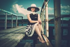 Stylish woman on old wooden pier Stock Photography