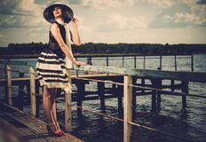 Stylish woman on old wooden pier Royalty Free Stock Image