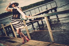 Stylish woman on old wooden pier Royalty Free Stock Photos
