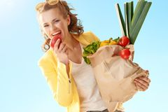 Stylish woman with paper bag with groceries biting apple a Royalty Free Stock Photos