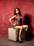Stylish woman posing on chair against grungy red background Royalty Free Stock Image
