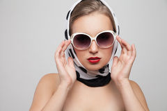 Stylish woman posing in sunglasses and scarf on. Young stylish caucasian woman posing in sunglasses and scarf on head, isolated over white, retro styling Royalty Free Stock Photo