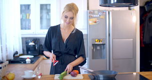 Stylish woman preparing dinner in the kitchen stock video