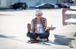 Stylish woman reading book on street ground and drinking coffee Stock Image