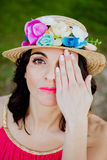 Stylish woman with a red dress and straw hat with flowers Stock Photography