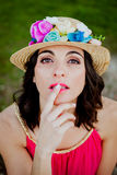 Stylish woman with a red dress and straw hat with flowers Stock Image