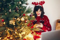 Stylish woman in reindeer hat holding phone and laptop, under ch. Ristmas tree lights. shopping online, sale. space for text. seasonal greetings, happy holidays Stock Photography