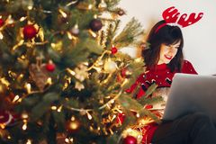 Stylish woman in reindeer hat with laptop,sitting under christma. S tree lights. shopping online,sale. space for text. seasonal greetings, happy holidays. merry Royalty Free Stock Image