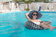 Stylish woman relaxing on a tube in a pool stock images