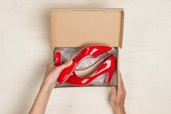 Stylish woman`s shoes in a box on wooden background Royalty Free Stock Photos