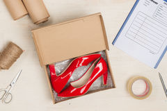 Stylish woman`s shoes in a box on wooden table. Royalty Free Stock Images