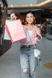 Stylish woman with shopping bags showing thumb up in mall Stock Photography