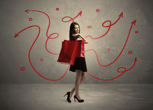 Stylish woman shopping and red arrows. An elegant young lady in black holding red shopping bags in front of urban wall background with drawn red arrows and Stock Image