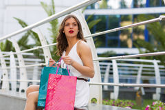 Stylish woman shopping in the summer city. Stylish woman with paper bags shopping in the summer city Stock Image