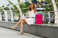 Stylish woman shopping in the summer city. Stylish woman with paper bags shopping in the summer city Royalty Free Stock Image