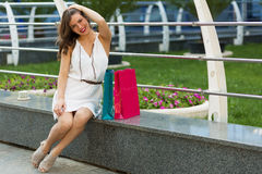 Stylish woman shopping in the summer city. Stylish woman with paper bags shopping in the summer city Royalty Free Stock Photos
