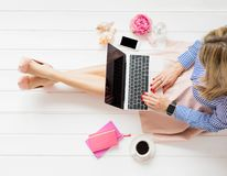 Stylish woman sitting on floor and using laptop stock photography