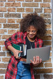 Stylish woman smiling while holding laptop and notebooks. Young stylish woman smiling while holding laptop and notebooks stock photo