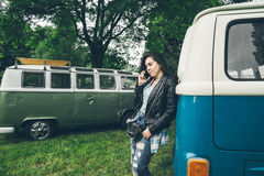 Stylish woman stand near retro van talking by phone Royalty Free Stock Images