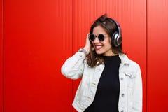 Stylish woman standing near red wall. Stylish young woman standing near the red wall Stock Images