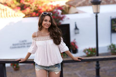 Stylish woman standing near wooden fence in old town Stock Photos