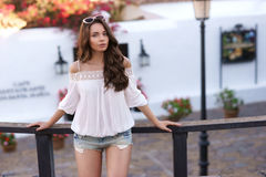 Stylish woman standing near wooden fence in old town Stock Photography