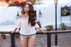 Stylish woman standing near wooden fence in old town Royalty Free Stock Photos