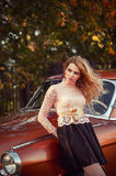Stylish woman standing with a retro car in fashion dress Stock Images