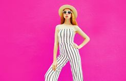 Stylish woman in summer round straw hat, white striped jumpsuit posing on colorful pink wall royalty free stock photo