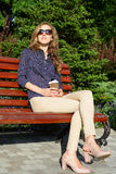 Stylish woman in sunglasses with disposable coffee cup sitting on bench Stock Photos