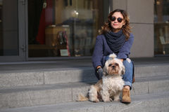 Stylish woman in sunglasses with shih-tzu dog sitting on the steps Royalty Free Stock Photo