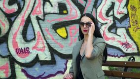 Stylish woman in sunglasses sitting on bench against wall with street graffiti. Stylish brunette in sunglasses and with red lipstick is posing for camera against stock video
