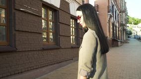 Stylish woman in sunglasses and trendy coat at the urban street. Elegant stylish woman in sunglasses, black dress and grey coat is walking at the urban street stock video
