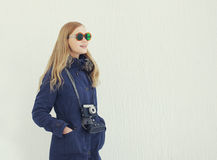 Stylish woman in sunglasses with vintage retro camera outdoors Stock Image