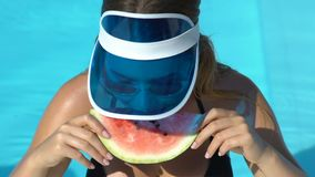Stylish woman in swimming pool eating watermelon slice and smiling, having snack. Stock footage stock video footage