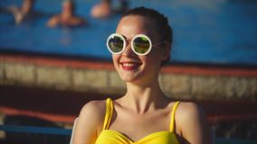 Stylish woman in a swimsuit and sunglasses smiling, sitting outside in summer stock video footage