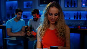 Stylish woman text messaging and two men sitting at table. At the bar 4K stock footage