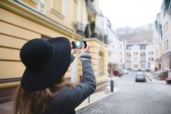 Stylish woman tourist makes a photograph of architecture. The girl is engaged in mobile photography. royalty free stock images