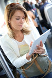 Stylish woman in tramway websurfing on tablet Royalty Free Stock Image