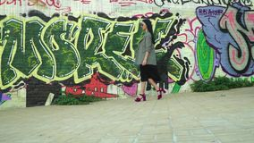Stylish woman in trendy clothes walking in slow motion near wall with graffiti. Elegance stylish woman in sunglasses, black dress and grey coat is walking at stock video footage