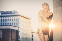 Stylish woman with urban sunset behind. Casual clothes, blonde hair and sensual attitude. stock photos