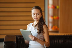 Stylish woman use modern technologies. Young girl sits with tablet Royalty Free Stock Photo