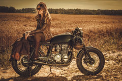 Stylish woman on the vintage custom cafe racer in a field. Stock Photo