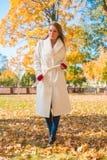 Stylish woman walking through an autumn park Stock Photos