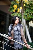 Stylish woman walking In the city in Fur-Vest. Urban street style, fashion trend. stock image