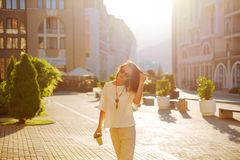Stylish woman walking with cup of coffee in city street. Stylish attractive brunette young woman walking with paper cup of coffee in city street royalty free stock images