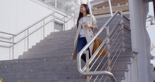 Stylish woman walking down a flight of stairs. Stylish young woman walking down a flight of stairs outdoors in an urban environment  view from below looking up Stock Image