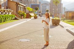Stylish woman walking with cup of coffee on the street. Stylish young woman wearing in white clothing walking on the street with paper cup of coffee in the royalty free stock image